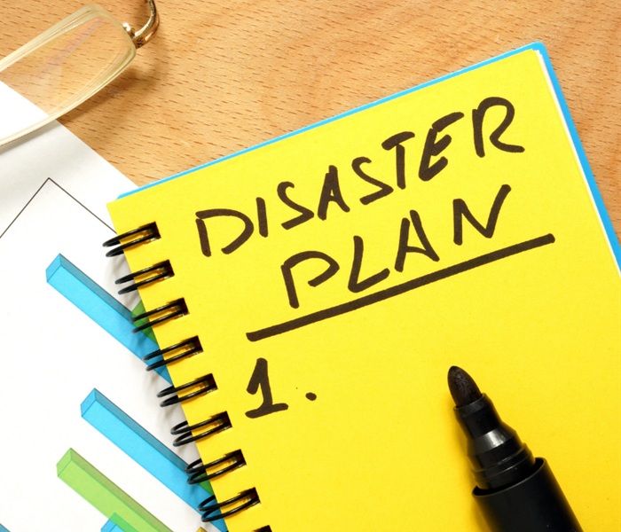 "Yellow paper with the words ""disaster plan"" written on it and a black marker laying on top of it."