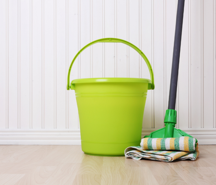 A lime green bucket and mop leaning against a white wall.