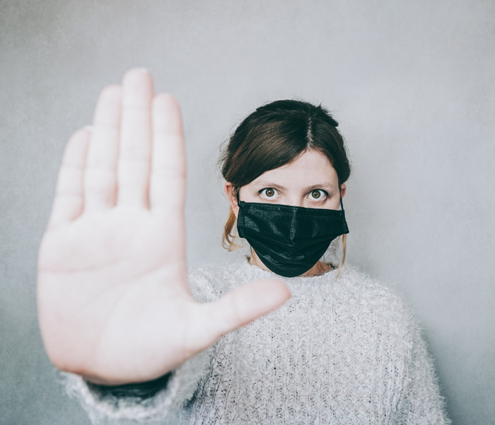 A woman wearing a black mask with her hand out indicating to someone to stop.