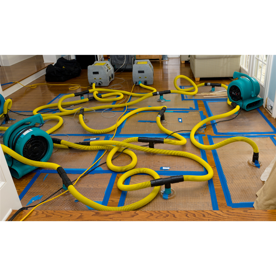 Blue fans with yellow hoses are connected to drying mats on the floor to help dry the wood flooring.